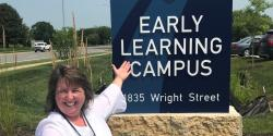 Staff member in front of the Early Learning Campus sign